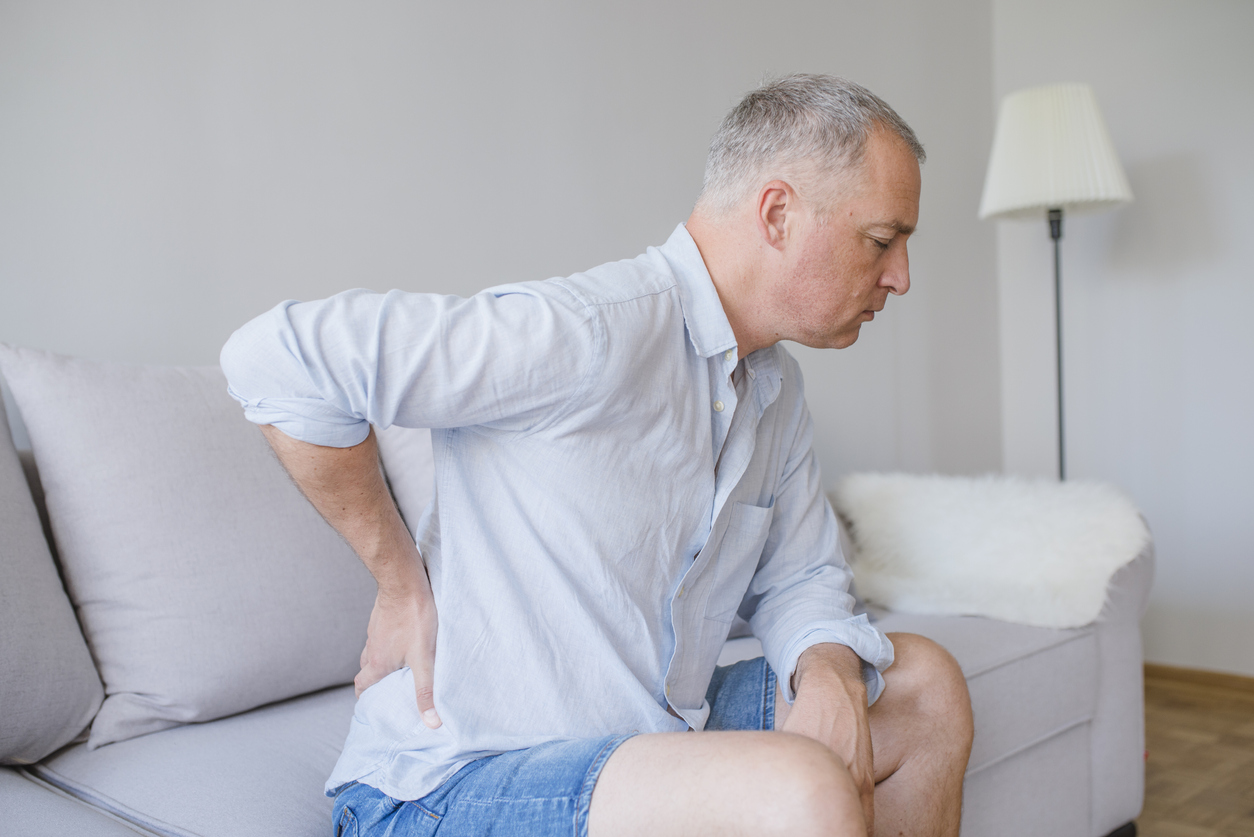 Lower back pain. Man holding his back in pain. Medical concept. Close up hands touching back pain. A man problem chronic low back pain, wondering do I have lower back pain.