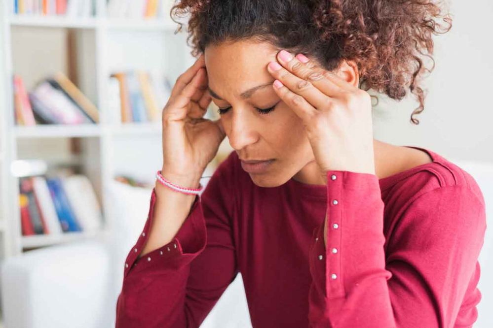 An African American female holding her head in pain, wondering if can a stroke cause pain.
