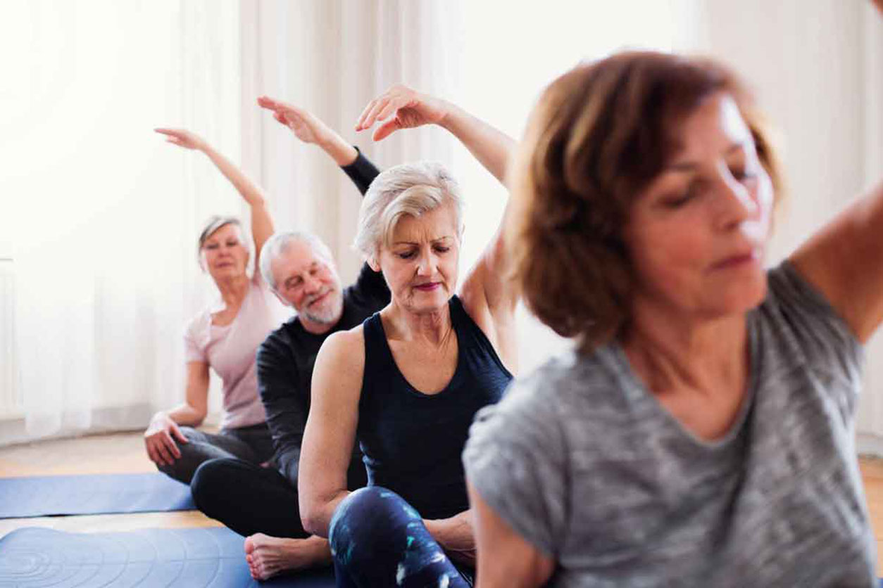 Seniors doing yoga, one of the examples of 5 Exercises Seniors Can Do to Stay Loose.