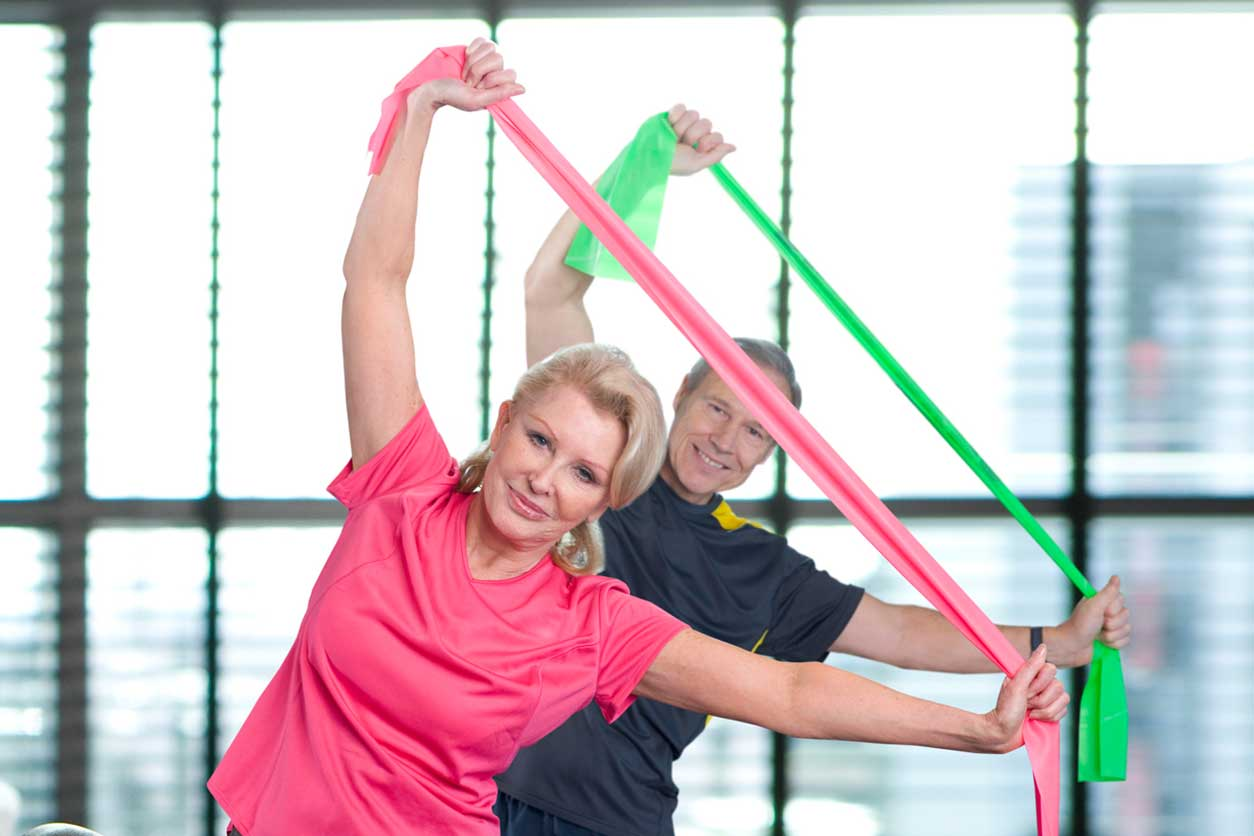 Elderly couple exercising with resistance bands, knowing how to stretch with resistance bands.