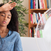 Black woman sitting in front of fan, hot weather affecting pain.