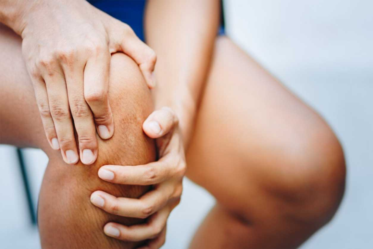 Person clutching knee in pain, sitting in chair, wondering living with knee pain.