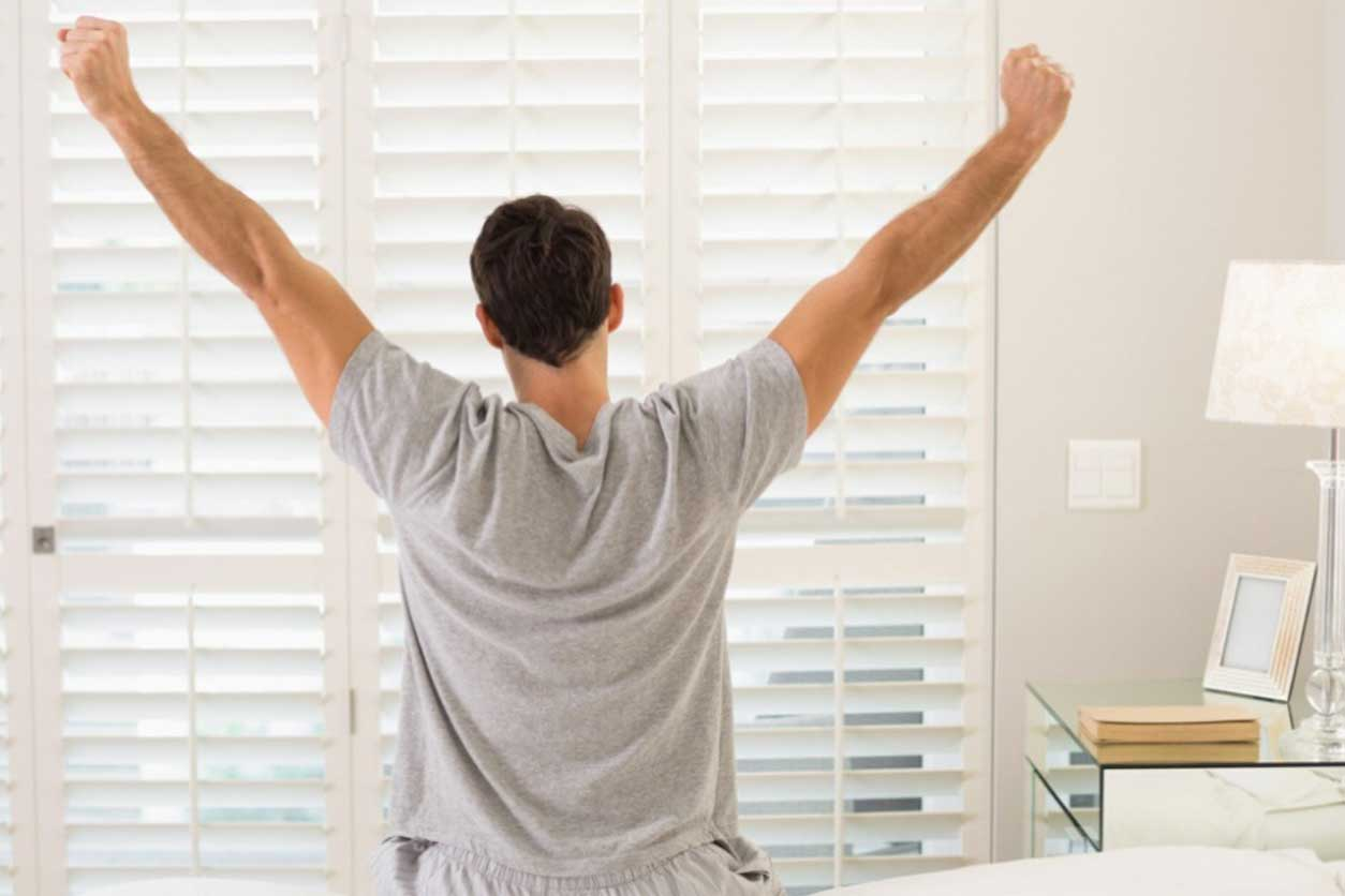 Man in gray shirt and sweatpants stretching while facing a window, knowing the benefits of stretching when you wake up.