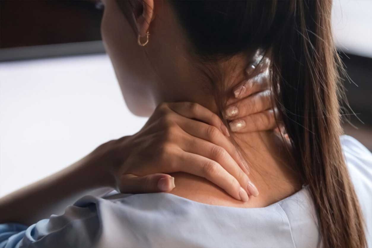Tired woman rubbing sore neck due to fibromyalgia pain.