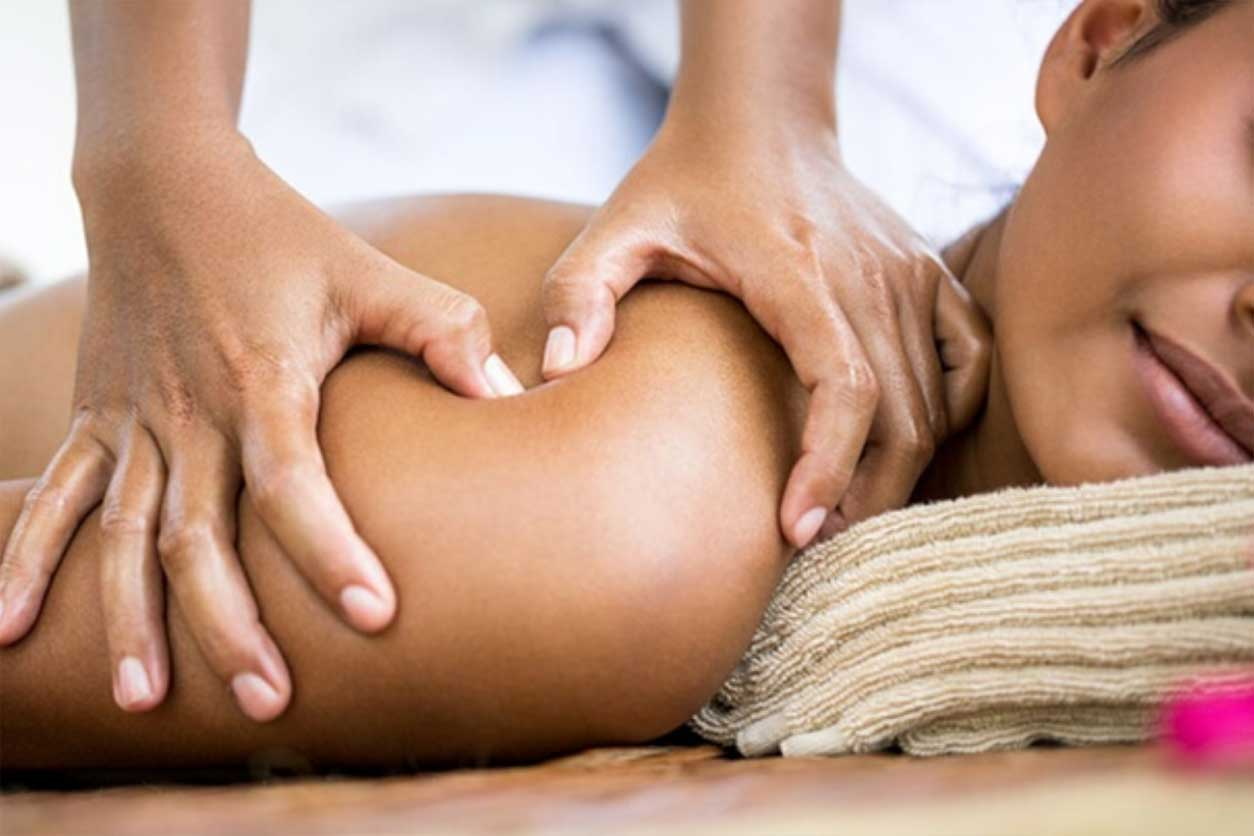 An African American woman receiving a massage, wondering about the benefits of a massage.