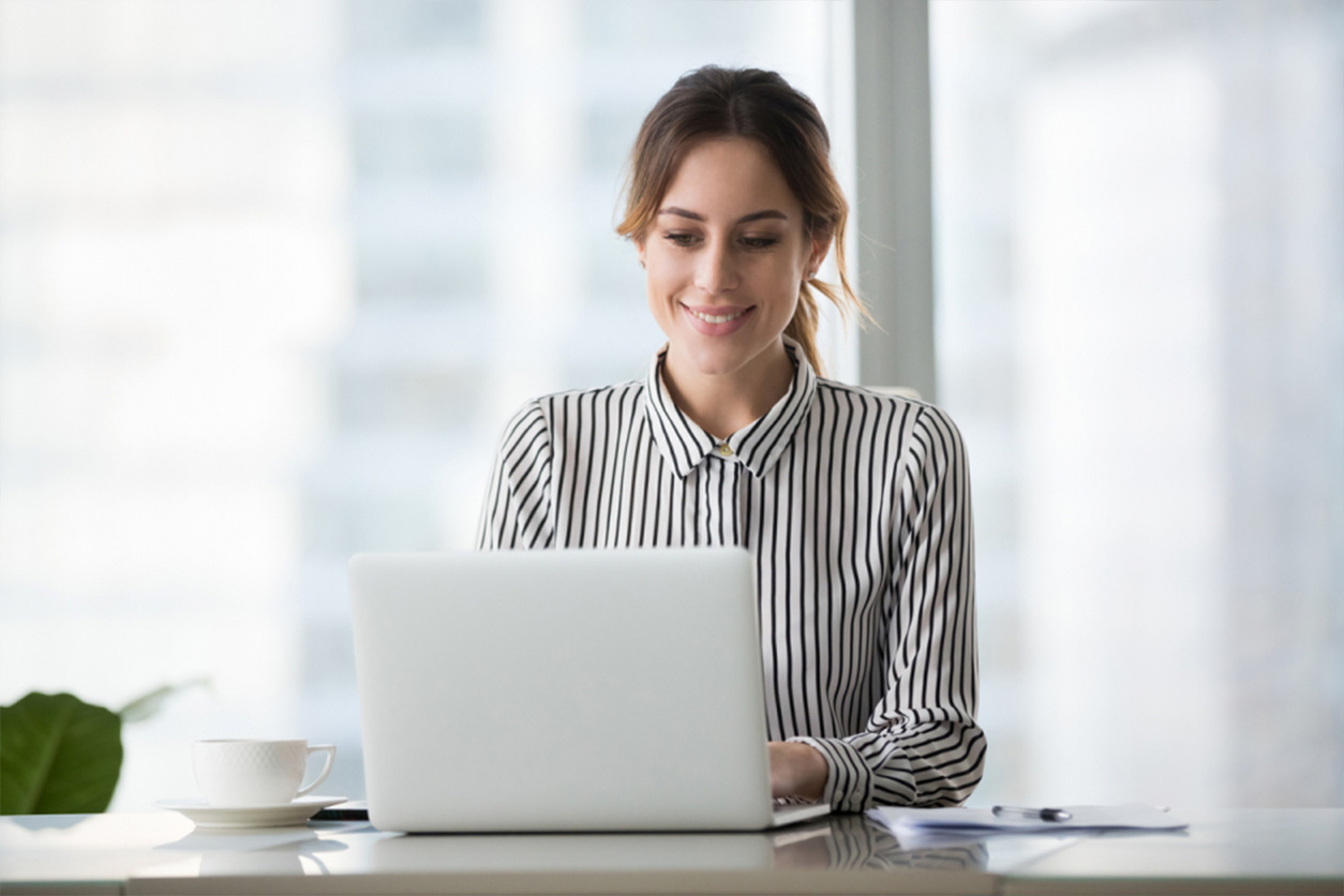 Happy business woman, professional worker, working online doing job on laptop at desk, smiling female employee executive typing message using corporate computer software for business in modern office.