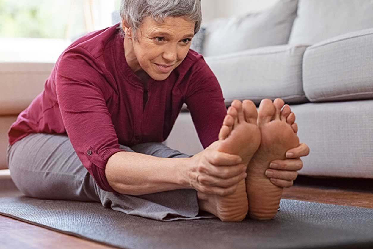 Older woman stretching over onto her feet, performing the best exercises for strengthening her back and spine.