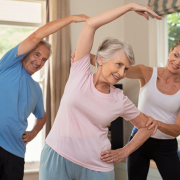 Senior couple doing exercise at home with physiotherapist, wondering how does the spine age.