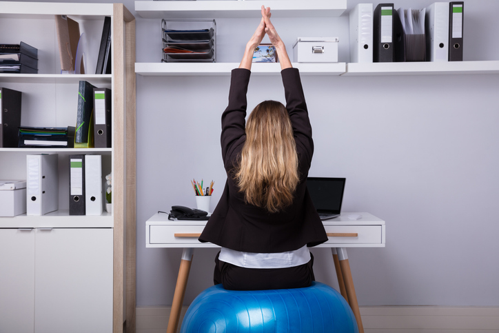 Rear View Of A Businesswoman Sitting On Fitness Ball Stretching Her Arms, working on her work posture.