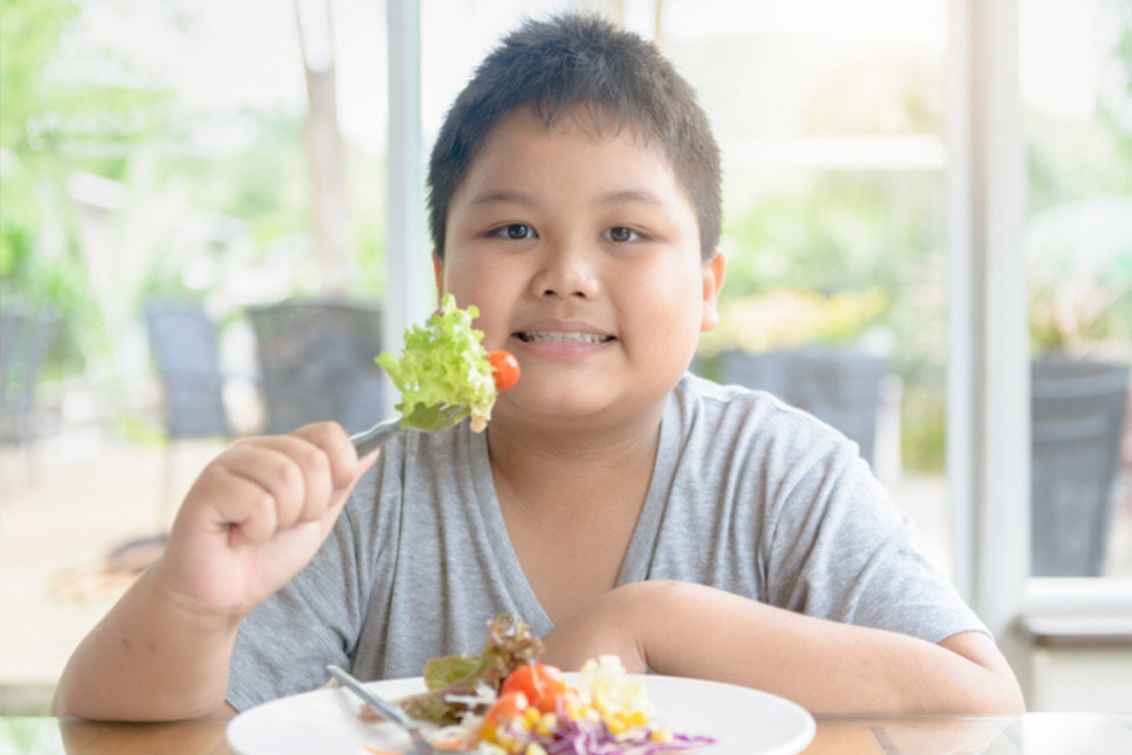Obese young boy on a diet, enjoying vegetables and salad, diet. Healthy food concept to fight against childhood obesity.