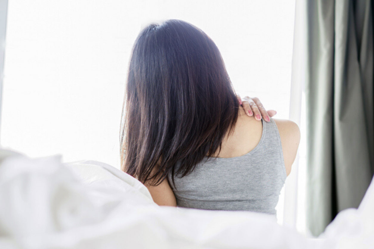 Asian woman upon waking up on bed, running shoulder due to a crick in neck from bad sleep posture.