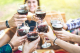 Hands toasting red wine and friends having fun cheering at winetasting experience - Young people enjoying harvest time together at farmhouse vineyard countryside - Foucus on glasses with blurred woman