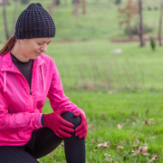 Young athlete woman hurting from a knee injury on a cold winter day in the track of an urban park, wondering How Your Pain is Affected By Cold Weather.
