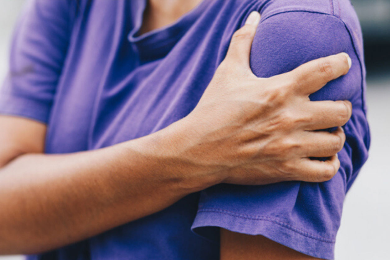 Young woman in purple shirt with pain on left shoulder, wondering the common reasons to visit pain specialists.