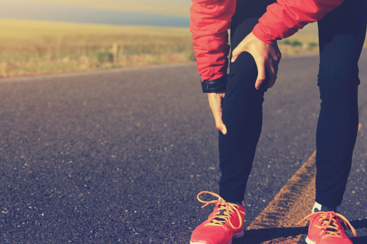 Woman holding sore joint while running in cold weather, wondering how does weather affects joint pain.
