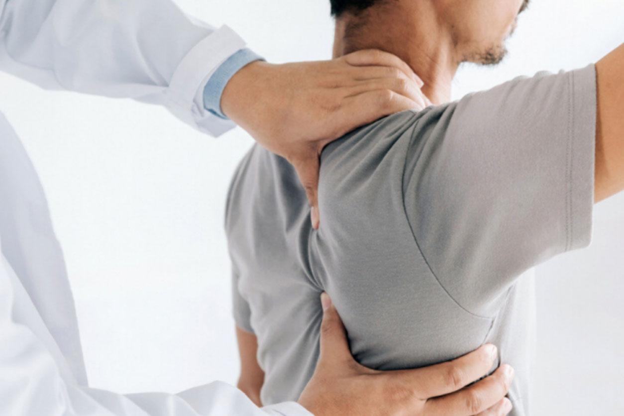 Physiotherapist doing healing treatment on man's back for medical conditions that can cause spinal pain