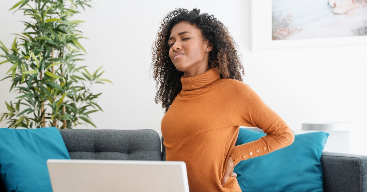 Young African American woman wearing an orange sweater experiencing back pain