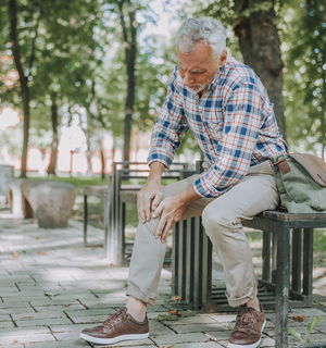 Older male sitting down in park, holding knee, in pain.