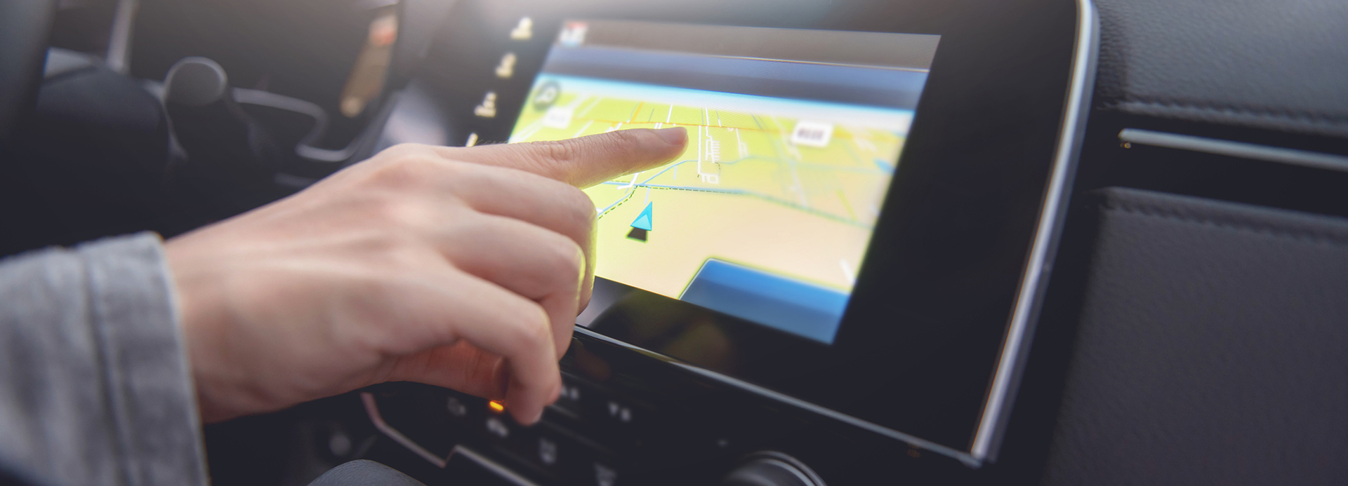 Person touching a GPS map in a car.