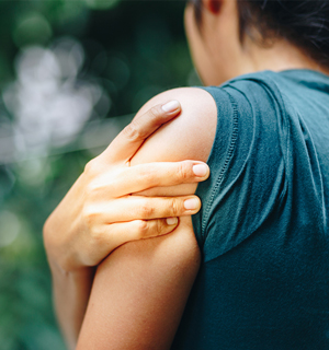 Female holding on to arm, in pain.