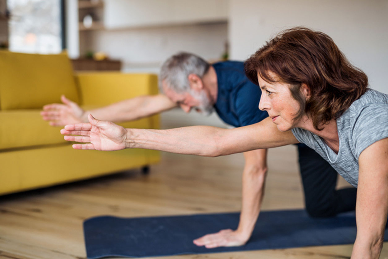 A happy senior couple indoors at home, doing exercise on the floor, wondering how to protect your body while working out at home.