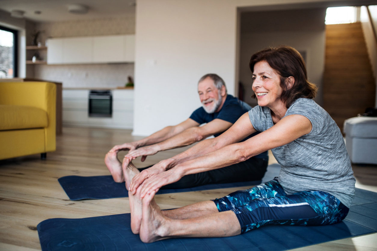 A happy senior couple indoors at home, doing exercise on the floor to strengthen their back.