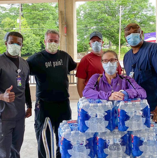 Community partners; picture of peple in masks with cases of bottled water
