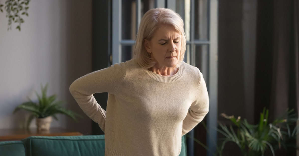 Older woman holding back in pain due to arthritis, wondering How Arthritis Affects Your Spine..