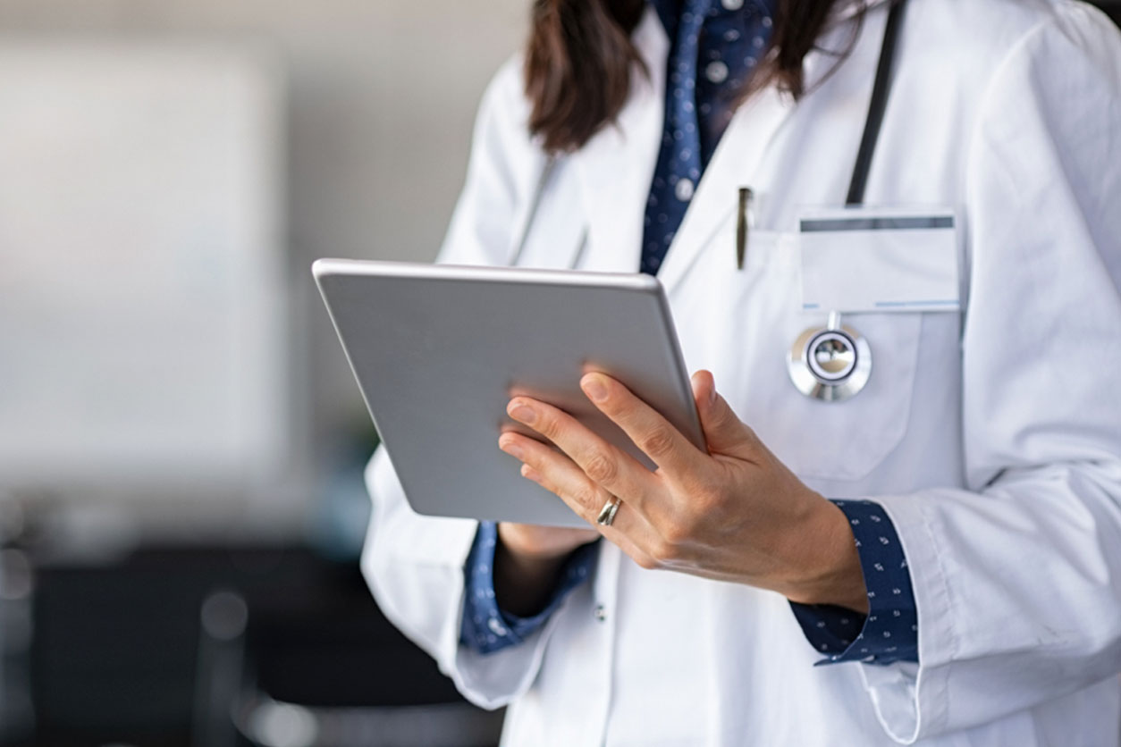Closeup of female doctor in labcoat and stethoscope holding digital tablet, reading patient report. Hands holding medical report, discussing Provocative Discography.