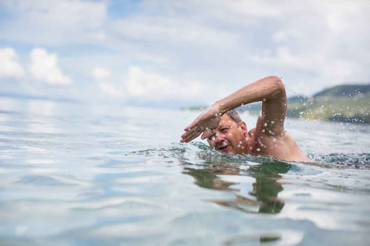 An elderly man swimming, wondering about the swimming exercises for a sore back here.