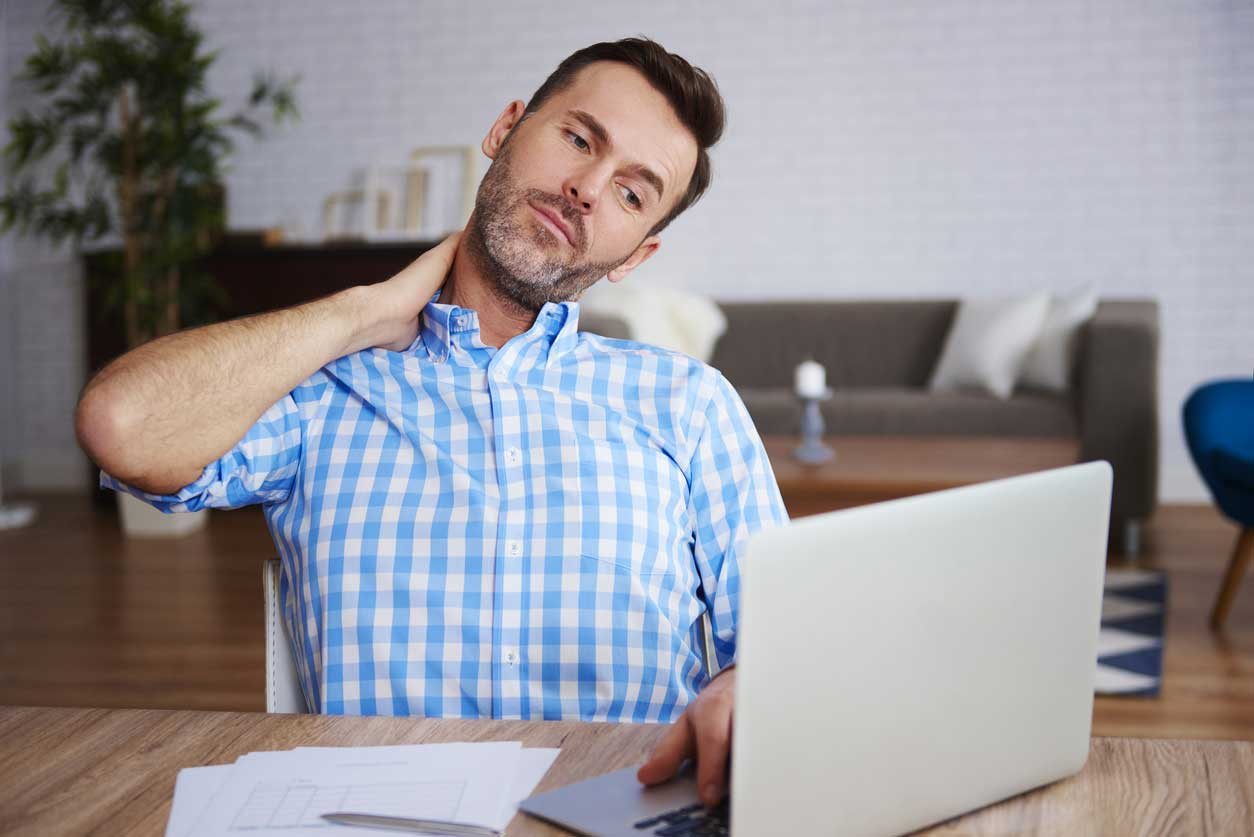 Man holding his neck in pain in front of the computer, wondering Is Your Chronic Pain Causing You to Look Older?