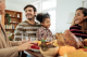 Smiling family enjoying a holiday meal together, discussinghow to avoid chronic pain flare-ups over the holidays.