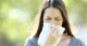 Girl sneezing and blowing her nose into a tissue