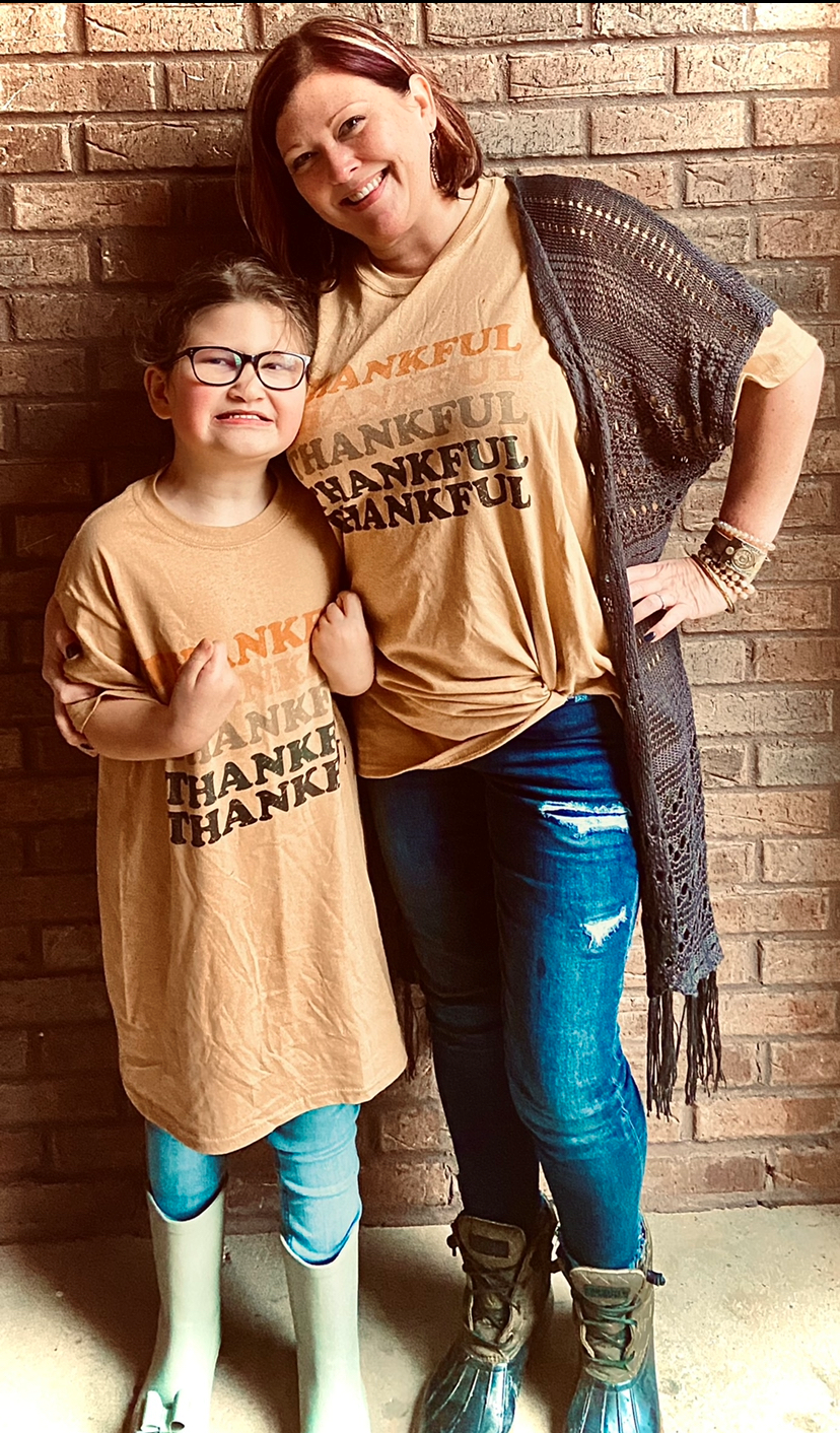 Woman and her daughter wearing matching tan t-shirt posing in front of a brick wall