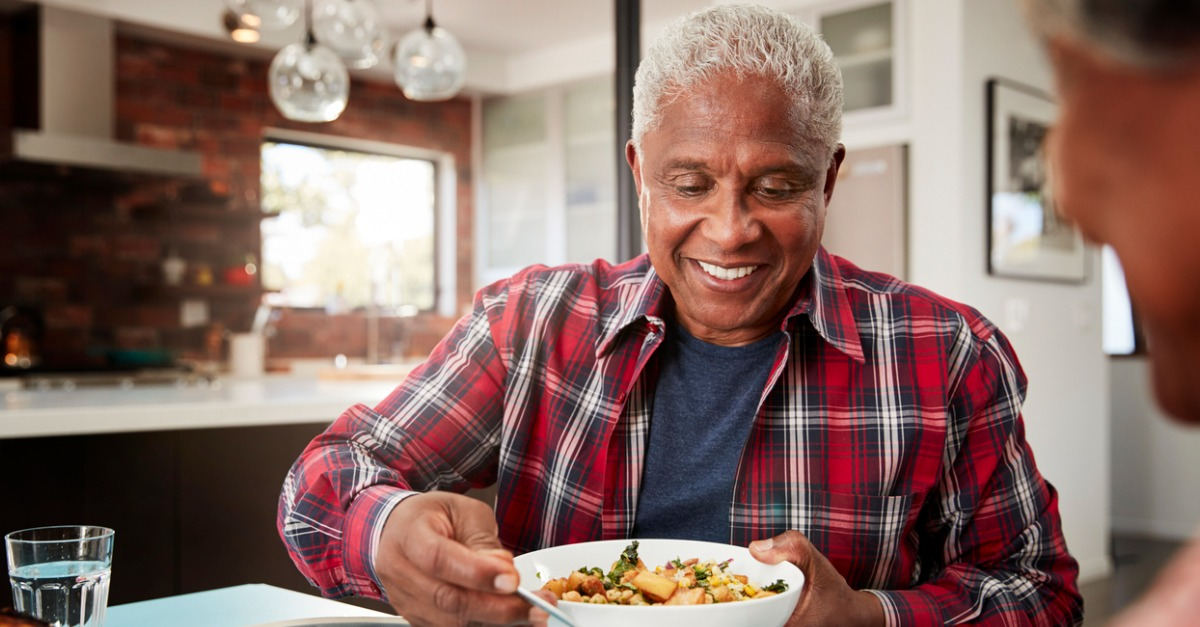 African American Senior Couple Enjoying Meal Around Table At Home