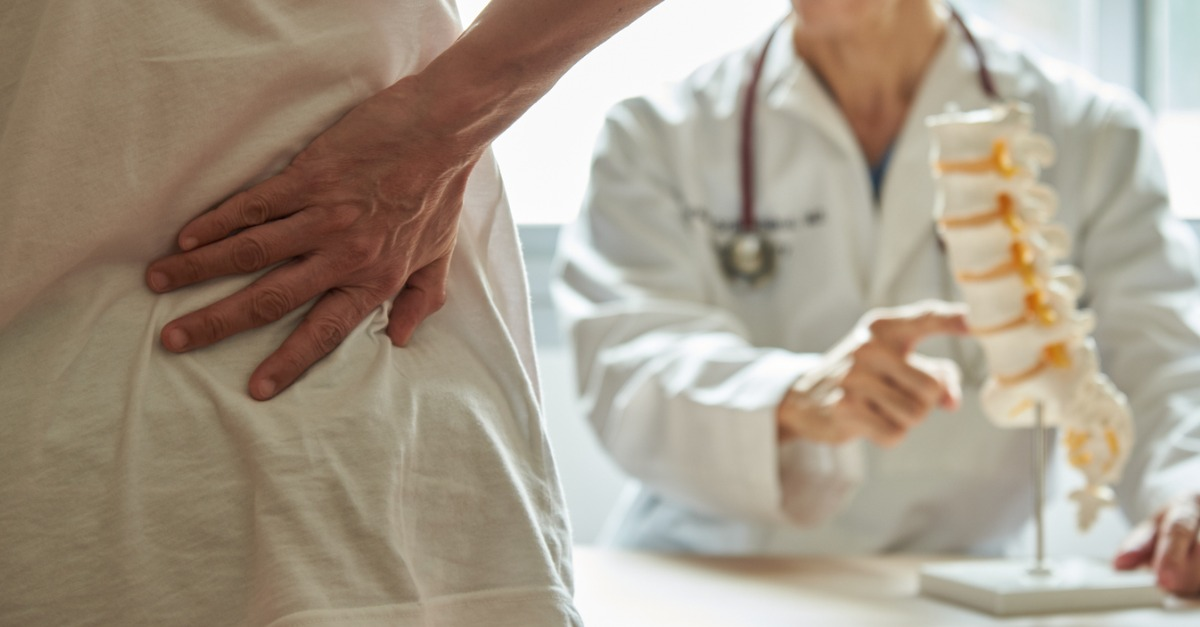 Patient with a hurt back standing in front of a doctor explaining a balloon kyphoplasty procedure