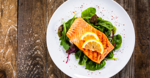 Grilled salmon on fresh vegetables on wooden table, chronic pain-friendly recipe
