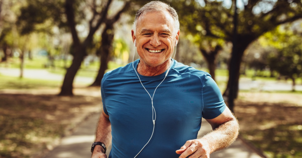 Athletic senior man in a blue t-shirt going for a jog outside.
